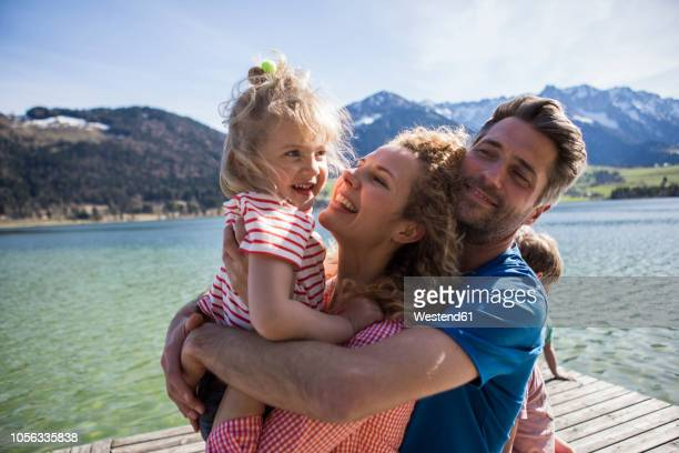 austria, tyrol, walchsee, happy family hugging on a jetty at the lakeside - family vacation stock pictures, royalty-free photos & images