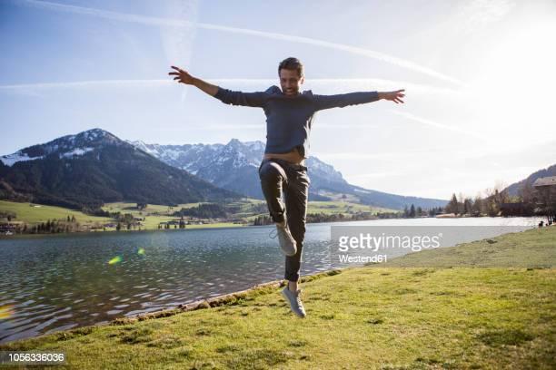 austria, tyrol, walchsee, happy man jumping at the lake - ausgestreckte arme stock-fotos und bilder