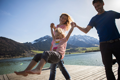 Austria, Tyrol, Walchsee, happy parents swinging their daughter at the lake - gettyimageskorea