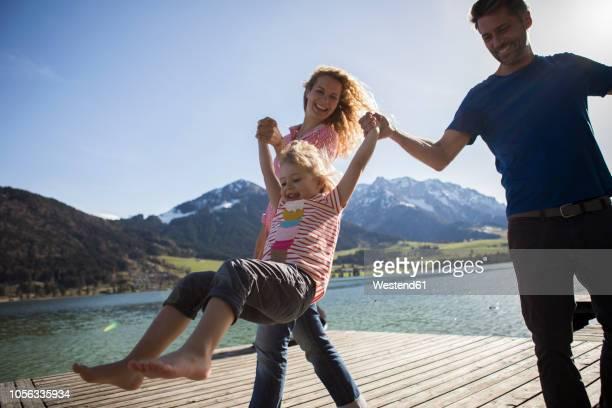 austria, tyrol, walchsee, happy parents swinging their daughter at the lake - familie mit einem kind stock-fotos und bilder