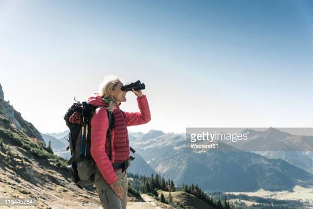 austria, tyrol, woman looking through binoculars during hiking trip - buitensport stockfoto's en -beelden