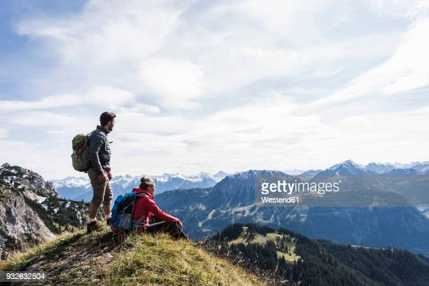 austria, tyrol, young couple in mountainscape looking at view - berg stock-fotos und bilder