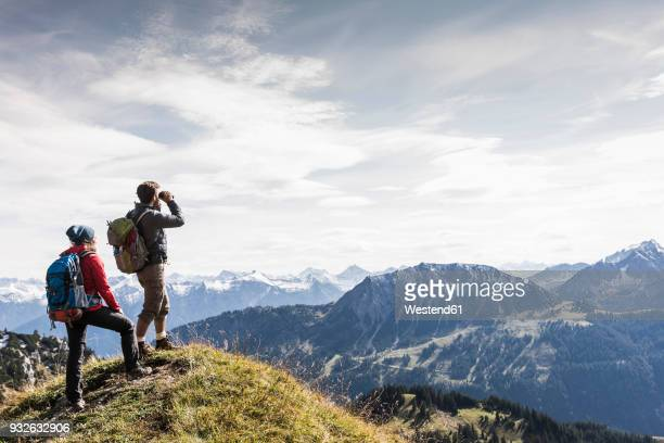 austria, tyrol, young couple standing in mountainscape looking at view - arrival photos stock photos and pictures