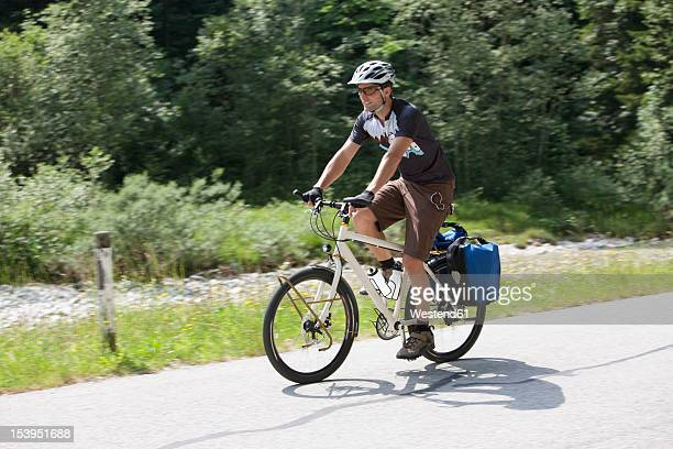Austria, Tyrol, Young man cycling through country road