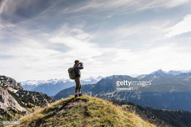 austria, tyrol, young man standing in mountainscape looking at view with binoculars - grand horizons stock pictures, royalty-free photos & images