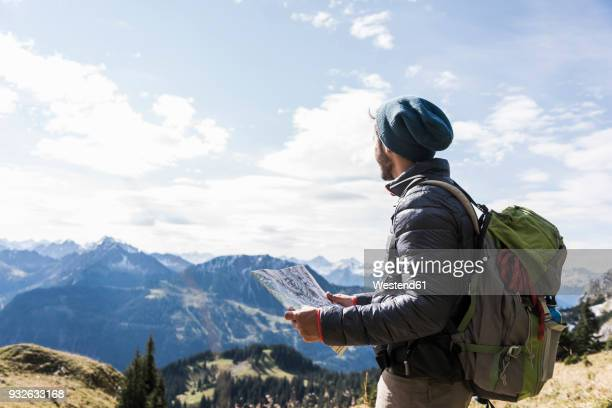 austria, tyrol, young man with map in mountainscape - karte navigationsinstrument stock-fotos und bilder