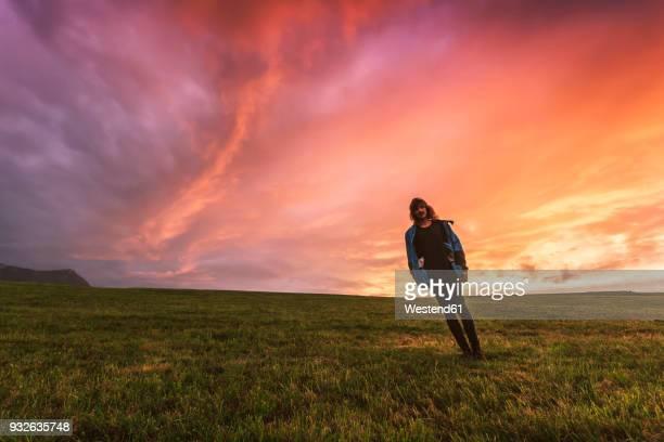 austria, upper austria, young man standing on meadow at sunset - schrägansicht stock-fotos und bilder