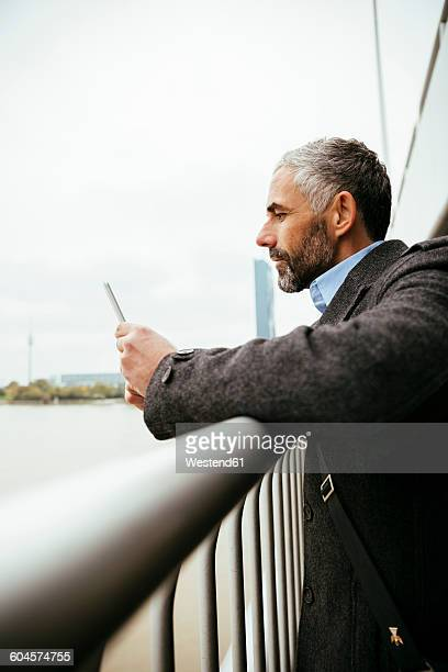 Austria, Vienna, businessman standing on Reichsbruecke looking at his smartphone