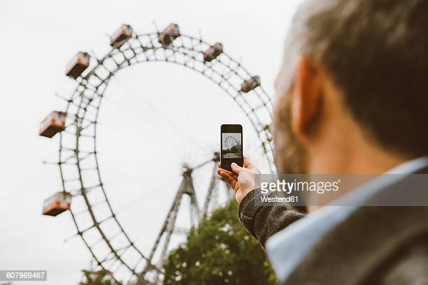 Austria, Vienna, businessman taking a picture of big wheel with his smartphone at Prater