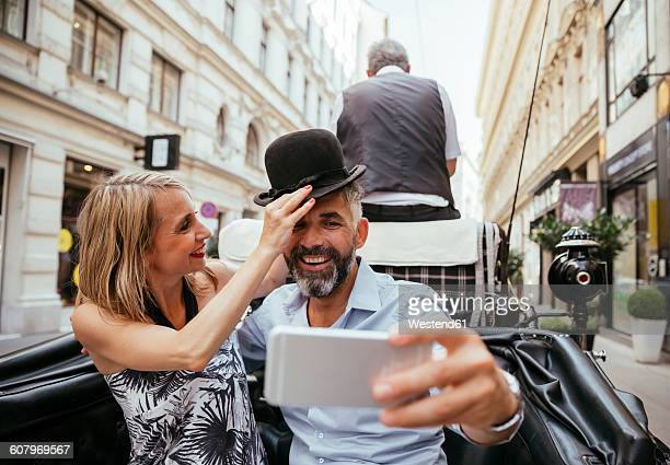 austria, vienna, couple having fun on sightseeing tour in a fiaker - carriage stock pictures, royalty-free photos & images