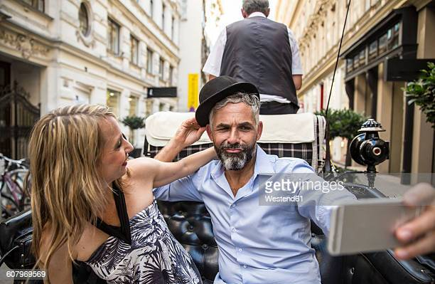 Austria, Vienna, couple having fun on sightseeing tour in a fiaker