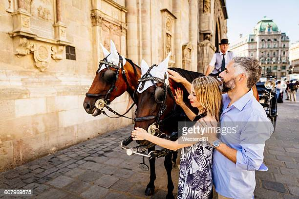 Austria, Vienna, couple stroking horse in front of St. Stephens Cathedral