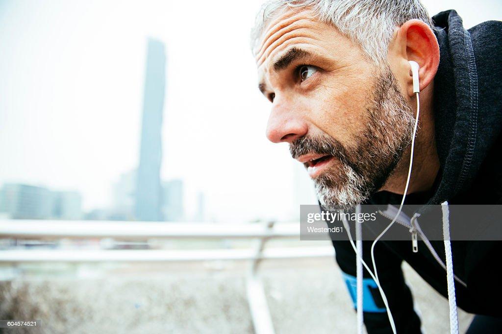 Austria, Vienna, exhausted athlete wearing earphones : Stock-Foto