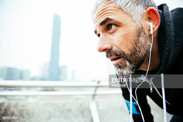 Austria, Vienna, exhausted athlete wearing earphones