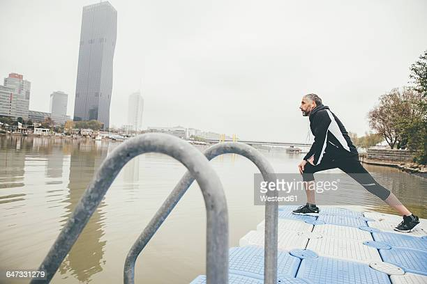 austria, vienna, jogger doing stretching exercise on danube island - precalentamiento fotografías e imágenes de stock