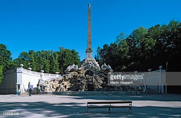 Austria, Vienna, Obelisk fountain at Schonbrunn palace with empty bench in the foreground