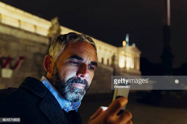 Austria, Vienna, portrait of man in front of parliament building looking at his smartphone by night