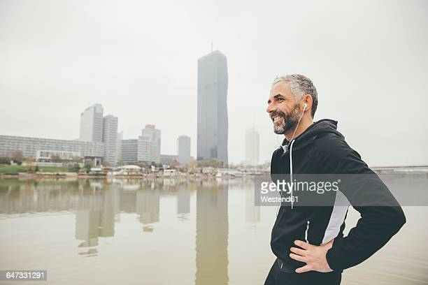 austria, vienna, portrait of smiling jogger with earphones in front of donau city - sportlichkeit stock-fotos und bilder
