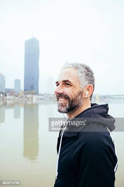 Austria, Vienna, portrait of smiling man with earphones on Danube Island