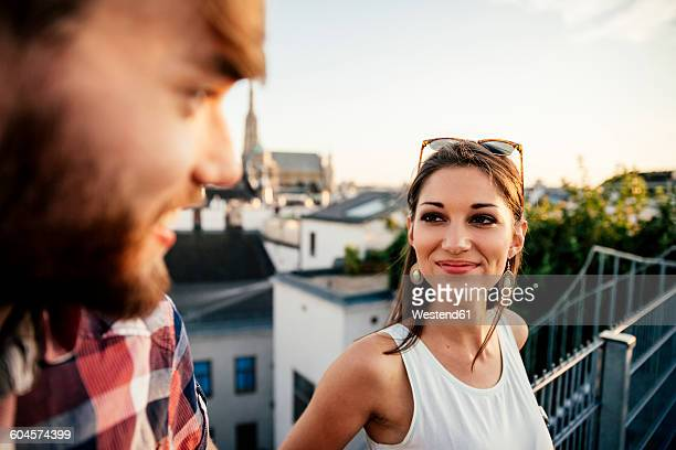 Austria, Vienna, portrait of smiling young woman face to face with her boyfriend on a roof terrace