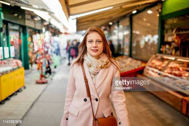 austria, vienna, portrait of smiling young woman shopping at naschmarkt - crossbody bag stock pictures, royalty-free photos & images