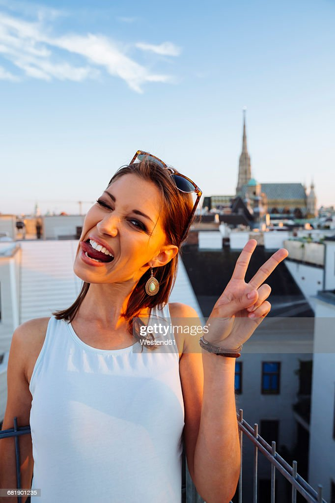Austria, Vienna, portrait of young woman on rooftop at sunset with Stephansdom in the background : Stock-Foto