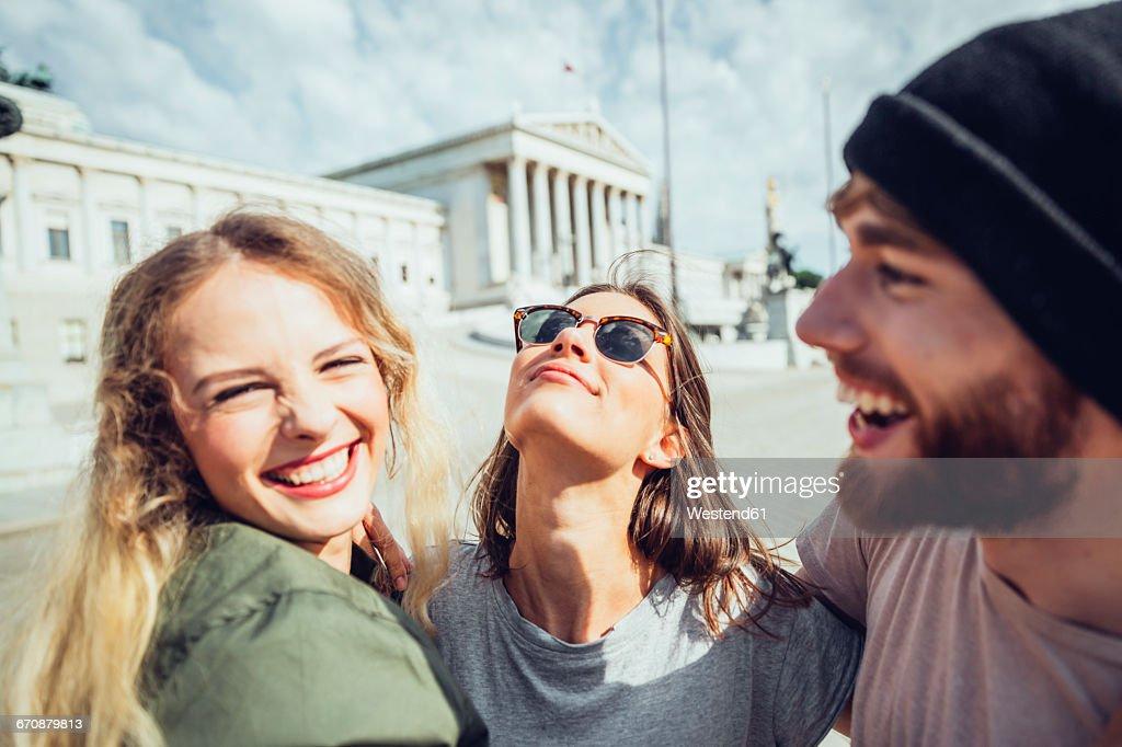 Austria, Vienna, three friends having fun in front of the parliament building : Stock-Foto