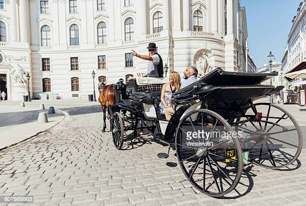 Austria, Vienna, tourists on sightseeing tour in a fiaker