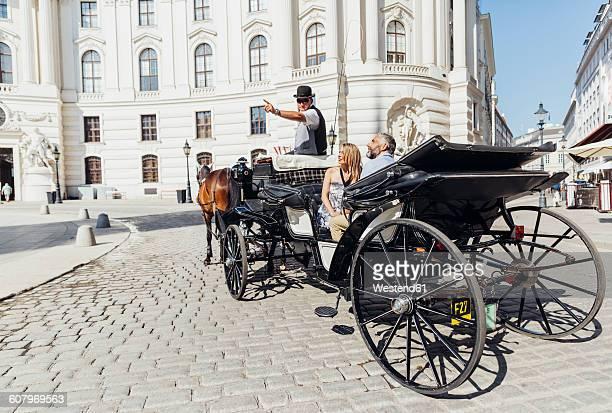 austria, vienna, tourists on sightseeing tour in a fiaker - vienna austria stock pictures, royalty-free photos & images