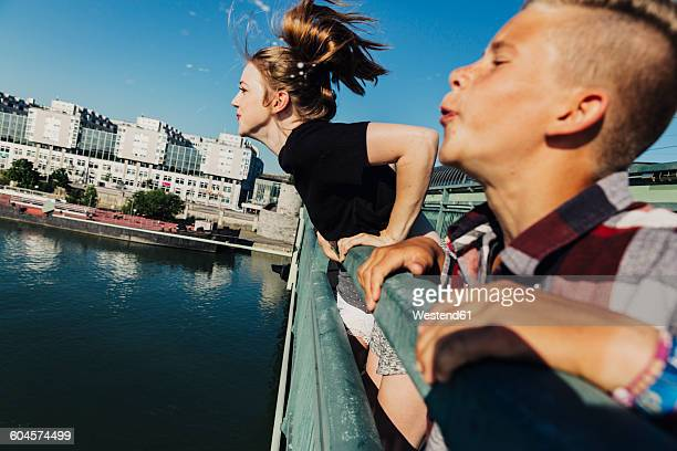 Austria, Vienna, two teenagers spitting from a bridge