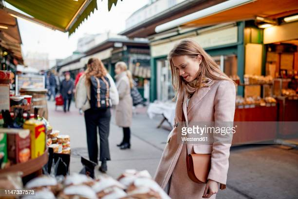 austria, vienna, woman looking at offer at naschmarkt - crossbody bag stock pictures, royalty-free photos & images