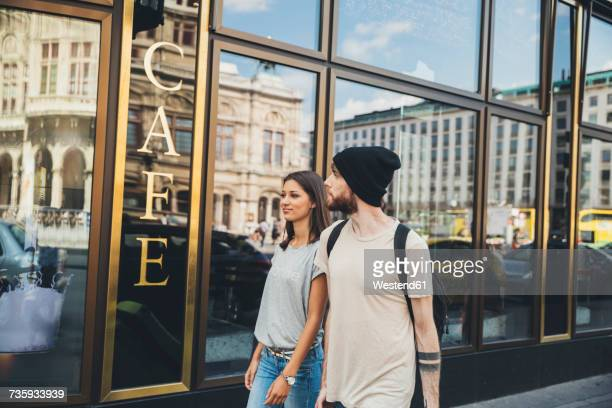Austria, Vienna, young couple walking in front of a coffee shop