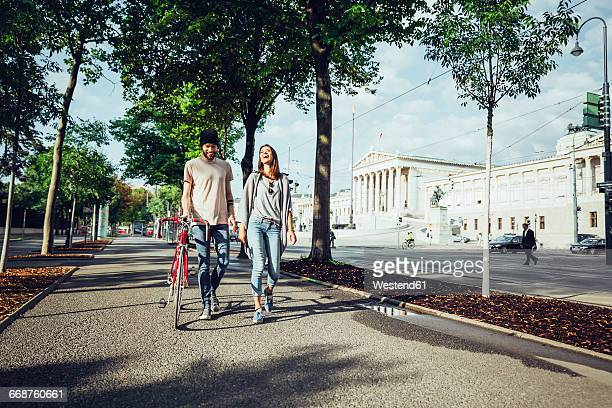 austria, vienna, young couple with bicycle in front of parliament building - wien stock-fotos und bilder