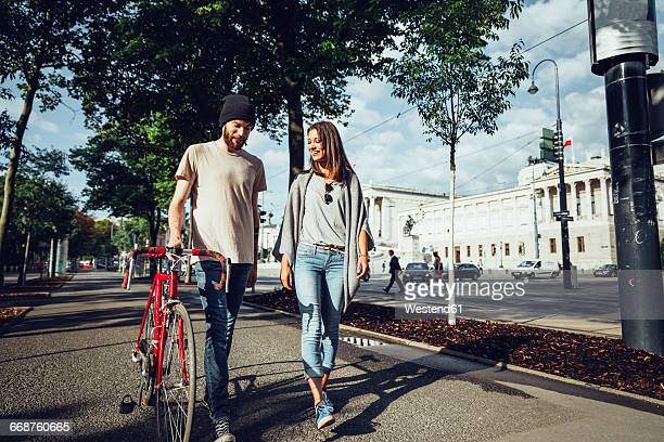 Austria, Vienna, young couple with bicycle in front of Parliament building
