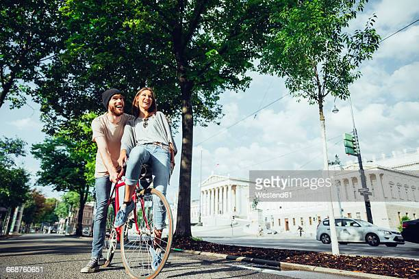 Austria, Vienna, young couple with bicycle near Parliament building