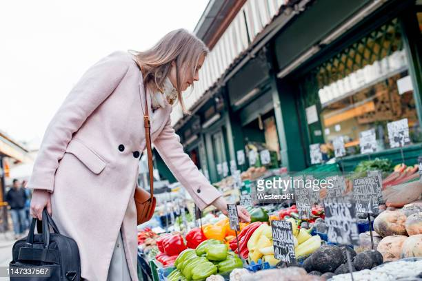 austria, vienna, young woman choosing vegetables at naschmarkt - green coat stock pictures, royalty-free photos & images