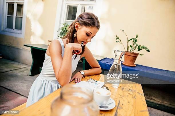 Austria, Vienna, Young woman sitting in Heurigen restaurant writing postcards
