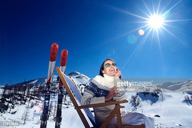 Woman sitting on deckchair in snow alps, smiling, low angle view
