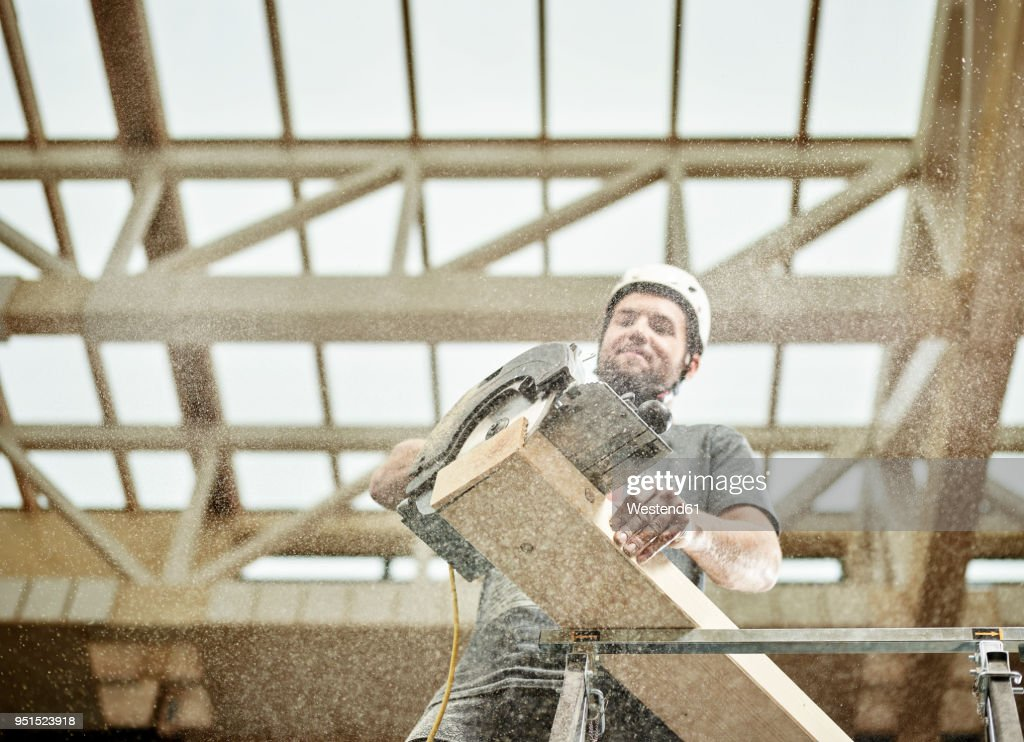 Austria, worker sawing wood : Stock Photo