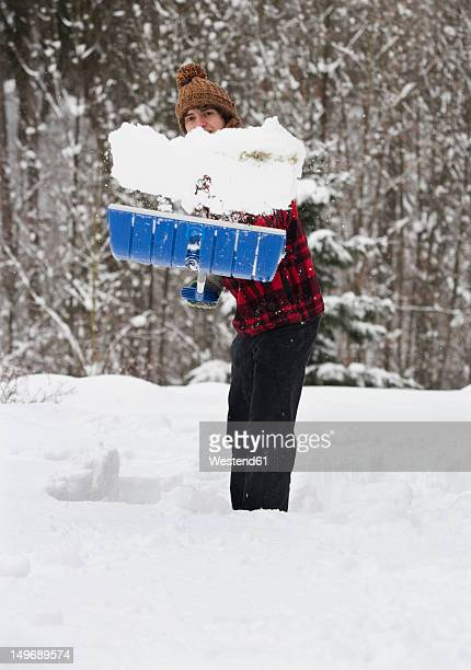 Austria, Young man shoveling snow, portrait