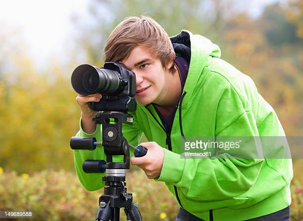 Austria, Young man taking photograph, smiling