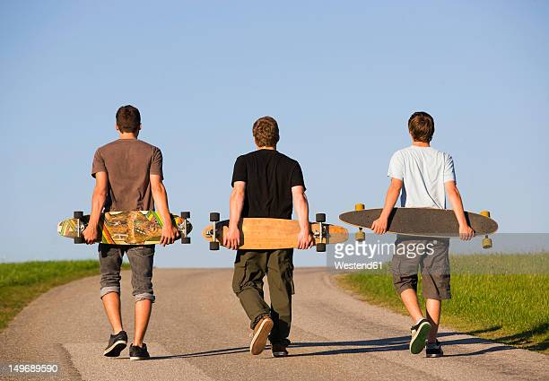 austria, young men with skateboard on road - longboard skating stock-fotos und bilder