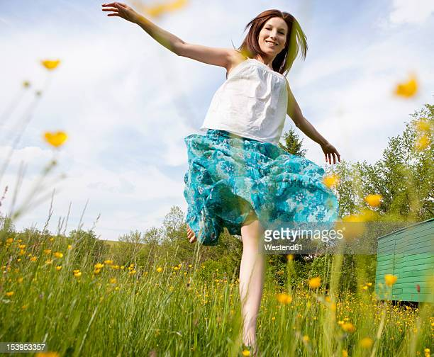 Austria, Young woman running in field of flowers