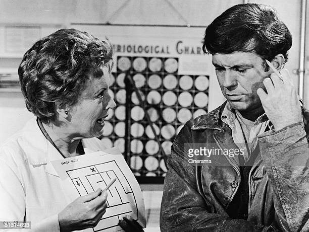 Austriaborn actress Lilia Skala holds an illustration of a maze as she talks to American actor Cliff Robertson in a scene from the film 'Charly'...