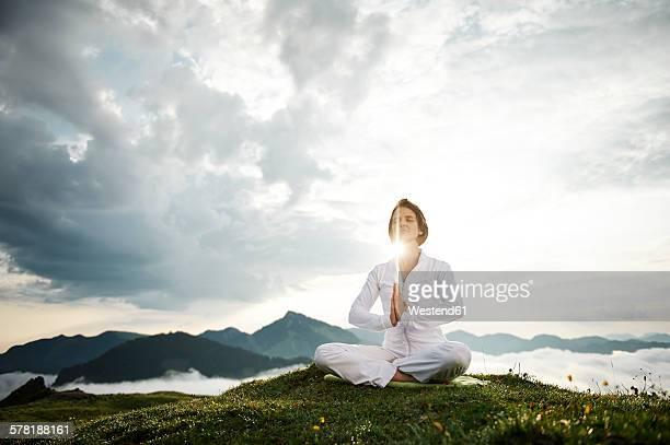Austria.Kranzhorn, Mid adult woman practising yoga on mountain top