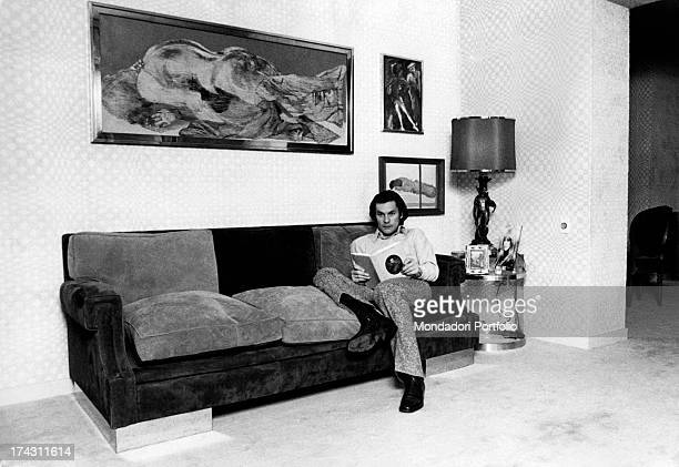 Austrian actor Helmut Berger sitting on a sofa holding a book Rome 1972