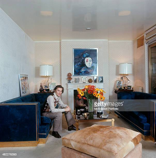 Austrian actor Helmut Berger sitting on the sofa in the living room of his house Rome 1972