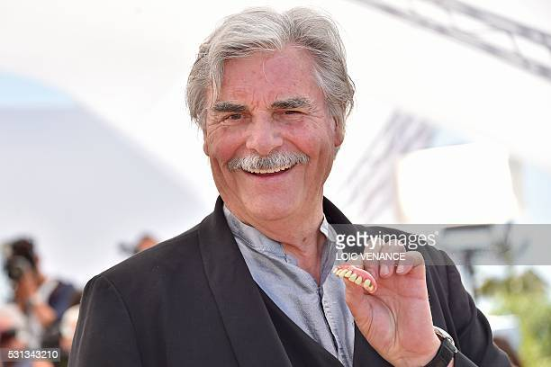Austrian actor Peter Simonischek holds prosthetic teeth on May 14 2016 during a photocall for the film 'Toni Erdmann' at the 69th Cannes Film...