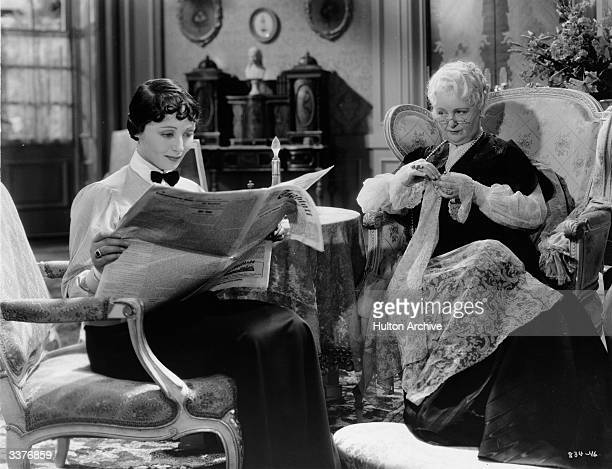 Austrian actress Luise Rainer sits reading a paper while her elderly companion works on her sewing in a scene from Escapade' directed by Robert Z...