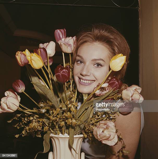 Austrian actress Maria Perschy who plays the character of Irena in the feature film 'The Password is Courage' posed beside a bowl of tulips in London...